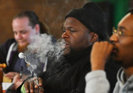 Detroit resident Jamal Williams smokes a marijuana cigarette during a visit to the Higher Limits Cannabis Lounge in Windsor, Ontario, Wednesday.  Customers can bring in marijuana and smoke it, but the lounge is not a dispensary.