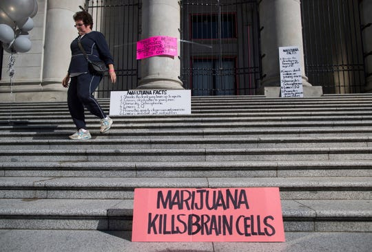 A woman who was part of a protest about the dangers of marijuana walks away after moving a sign in Vancouver, on Wednesday, Oct. 17, 2018. Canada became the largest country with a legal national marijuana marketplace as sales began early Wednesday.