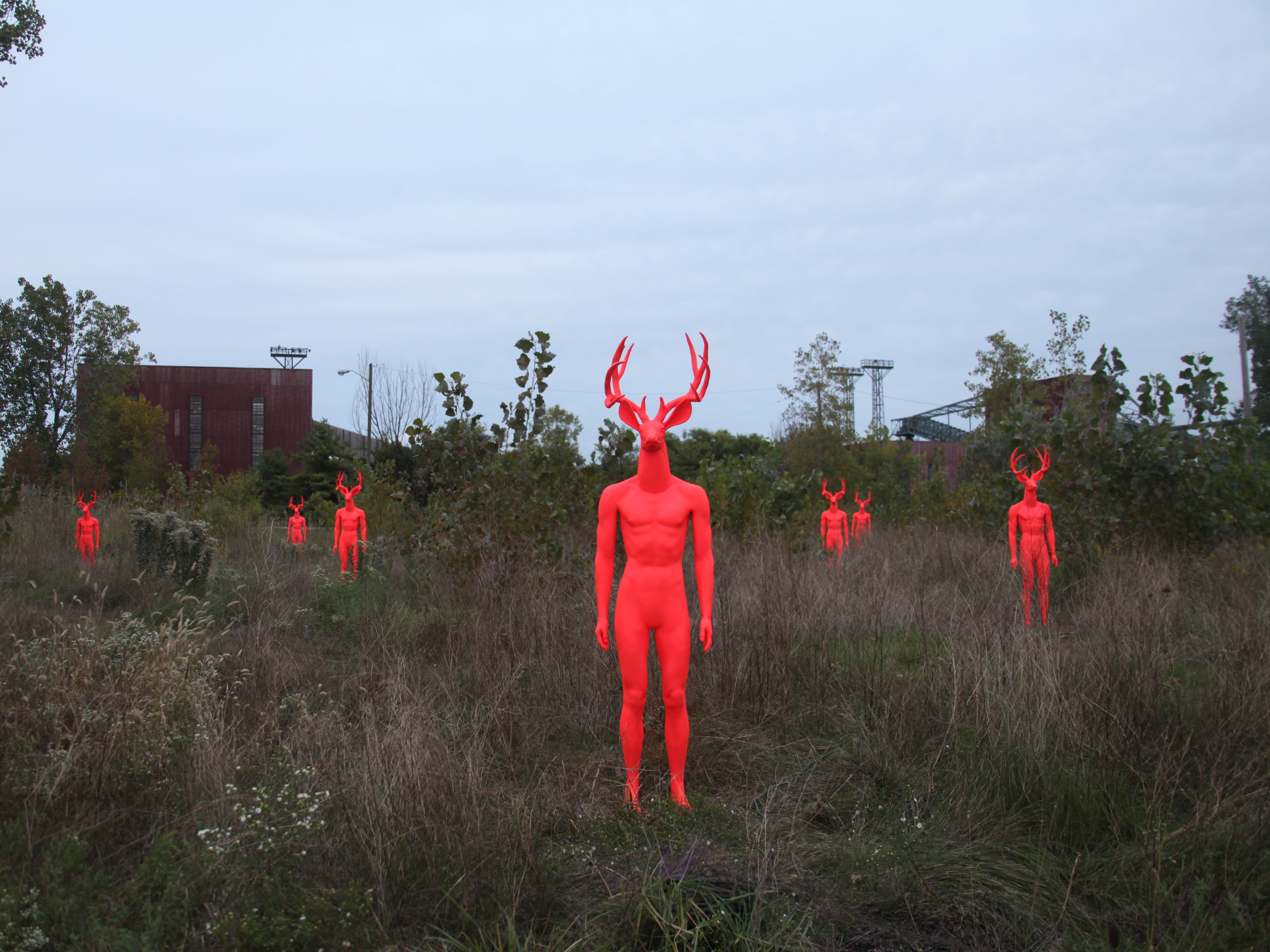 """Titled """"Spirit of the Forest,"""" the seven cast aluminum human-like figures with deer heads are individually illuminated by UV footlights. They are scattered throughout an overgrown field and appear to be emerging toward the viewer on a semi-circular footpath flanked by huge concrete planters."""