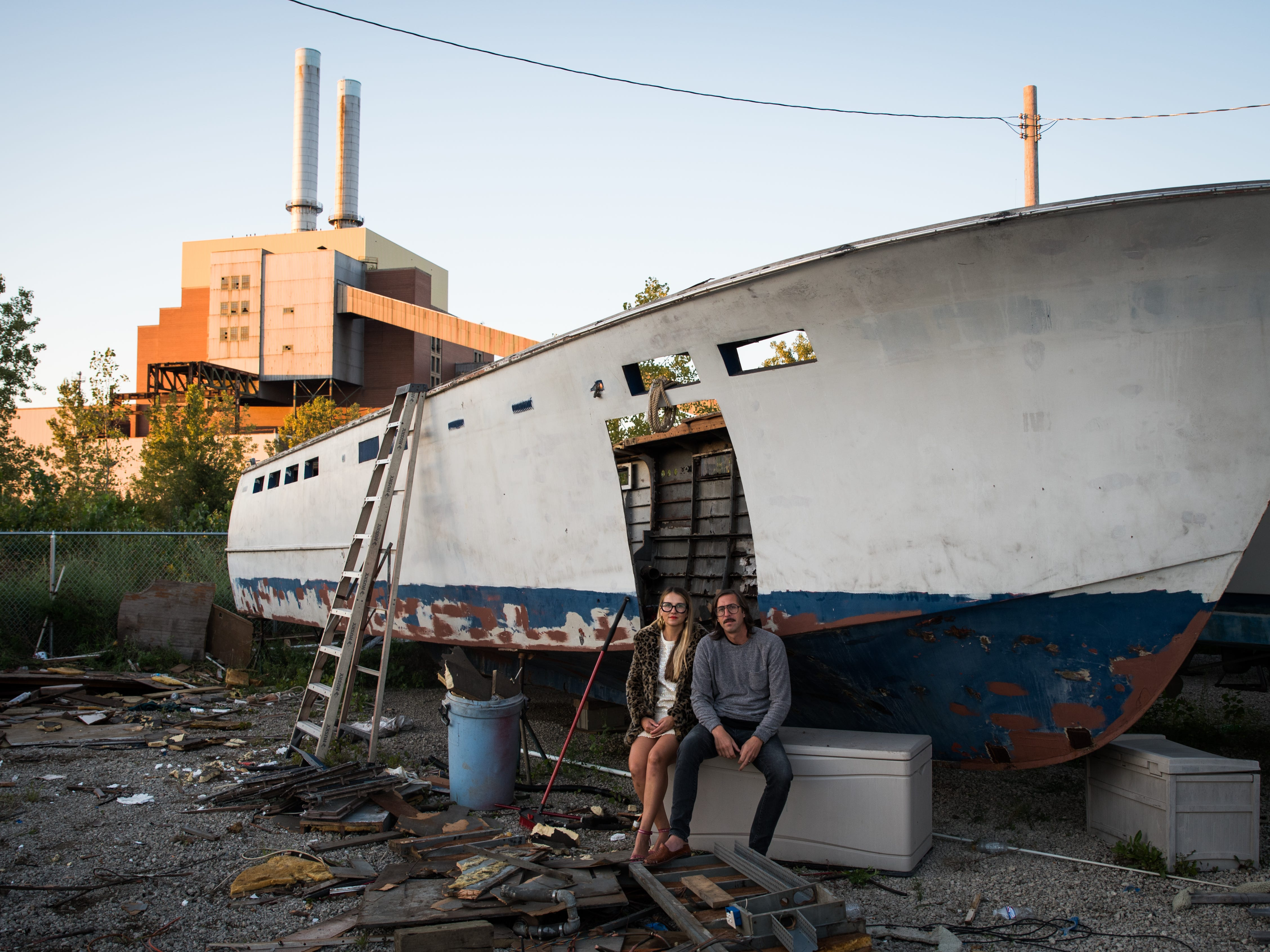 Conceptual artists Dorota and Steve Coy relax in front of an old ship on the site, one of the largest riverside tracts eligible for redevelopment. The DTE plant was shut down when nuclear power plant Fermi 2 rendered the coal-powered facility obsolete.