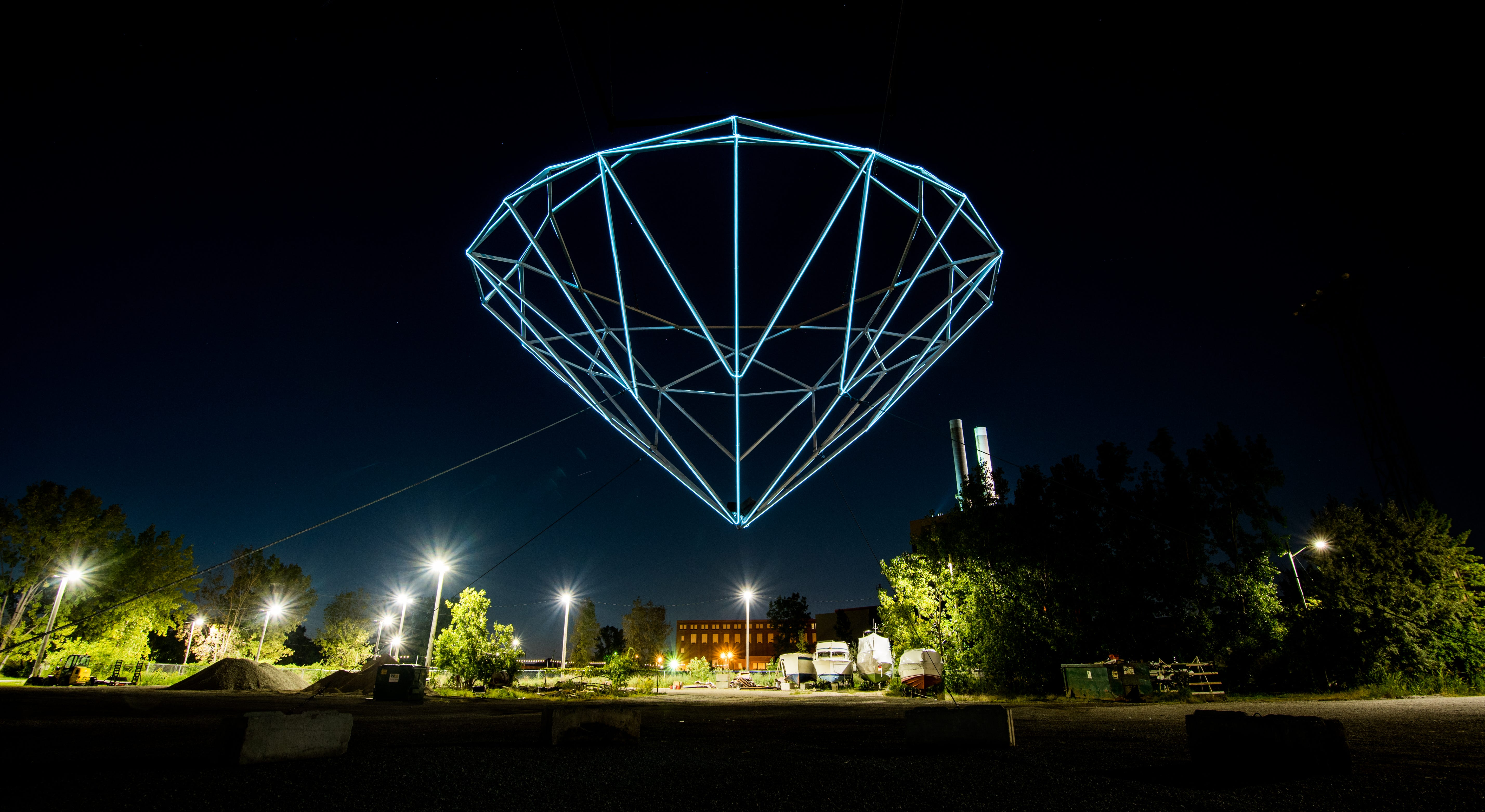 """""""Diamond II,"""" a 24-foot, diamond-shaped light installation, is suspended over a waterfront site where the Conners Creek DTE plant used to stand on the Detroit River. The Edison Boat Club, a marina for DTE employees, remains in use. The artist-duo known as Hygienic Dress League has three large-scale works at the site, intended to explore the ideas of superficial value vs. real value, among others."""