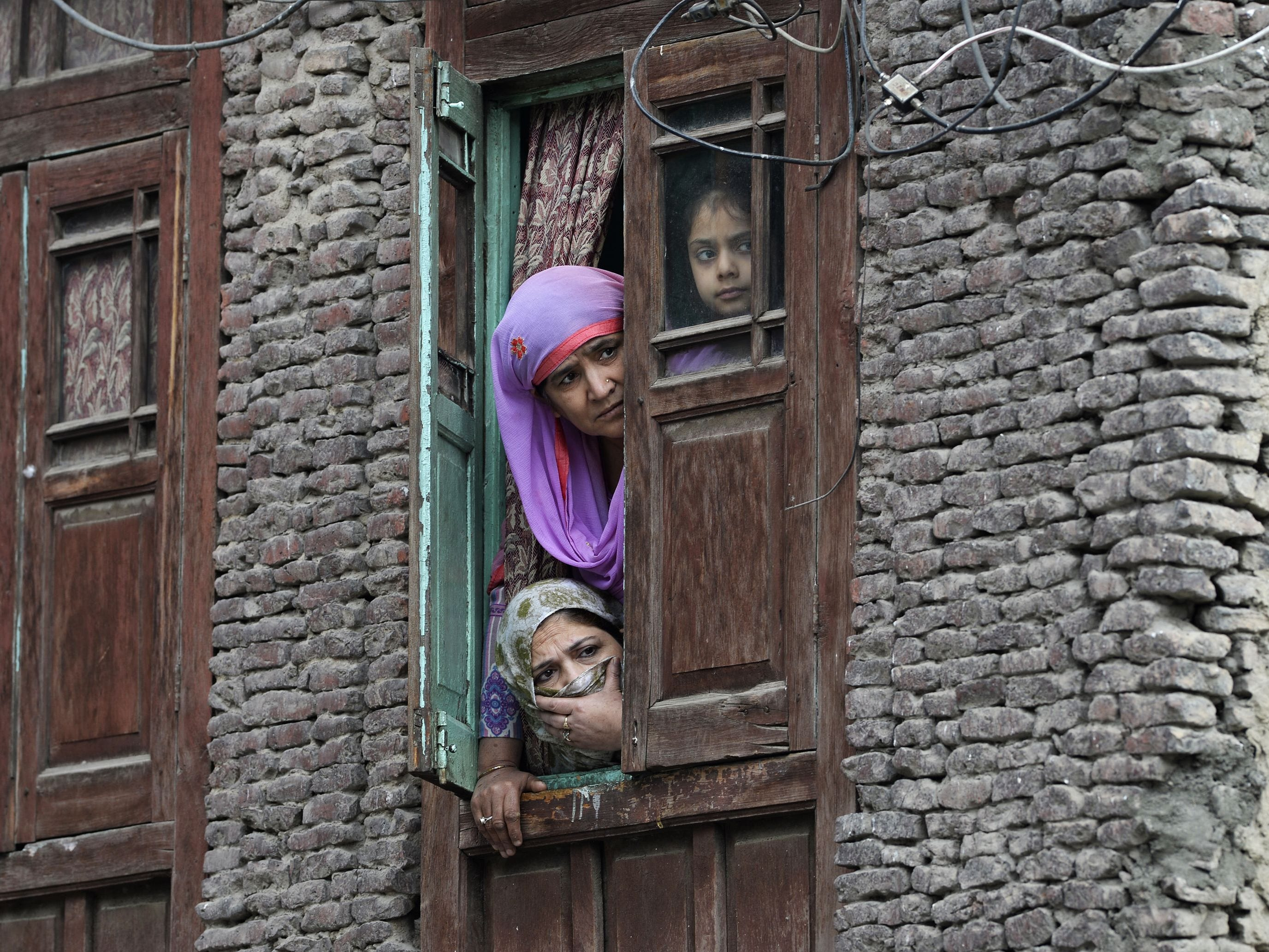 Residents look out from a window near the site of a gun battle between suspected militants and Indian government forces in downtown Srinagar on Oct. 17, 2018. Two suspected militants and one security force personnel were killed, officials said.