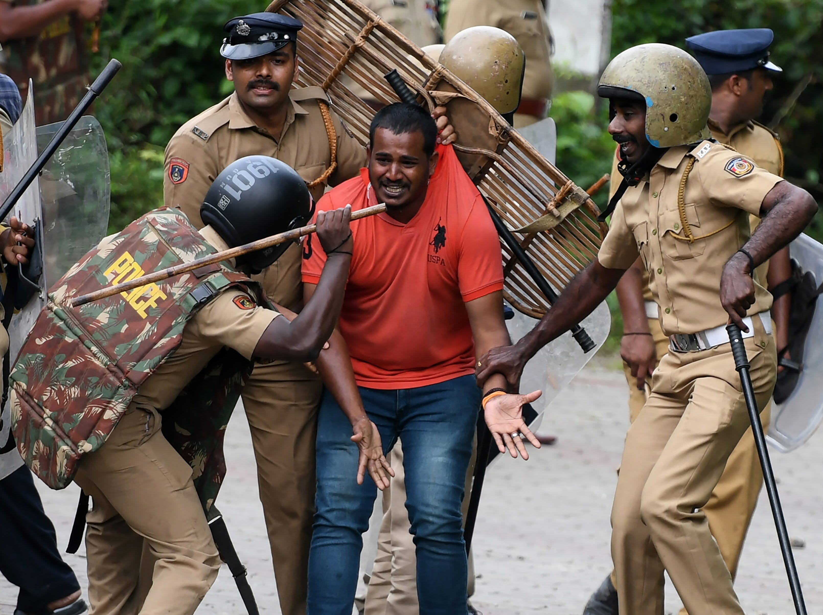 Indian police beat a Hindu activist as he pleads for his safety amid protests against a Supreme Court verdict revoking a ban on women's entry to a Hindu temple, in Nilackal in southern Kerala state on Oct. 17, 2018. Clashes erupted in India as traditionalists tried to stop women from visiting one of Hinduism's most sacred temples, with police waving batons charging stone-throwing protesters.