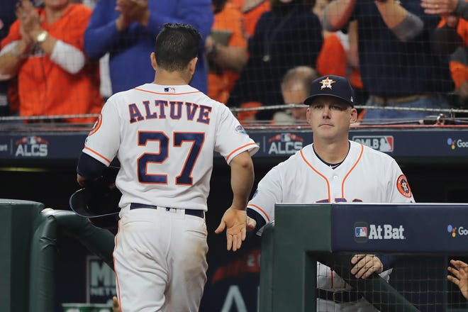 Jose Altuve celebrates with manager AJ Hinch after scoring a run in the first inning of Game 3.