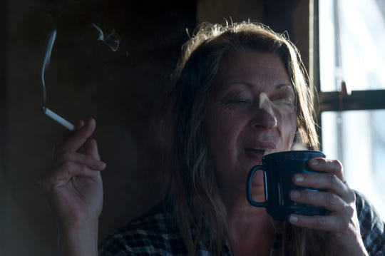 Valerie Hufford enjoys a coffee and a cigarette from the warmth of her RV on Dec. 10, 2017. Sunday mornings at the river are Hufford's last chance to take in the peacefulness of the camp before returning to the city.