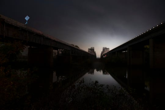 "City lights brighten the sky above the Twin Bridges that link Kentucky and Indiana on Nov. 4, 2017. The self-proclaimed ""river rats"" often venture near the bridges to explore."