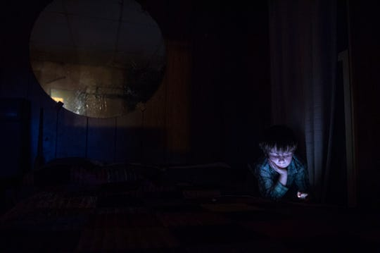 Xavier Short, 7, plays on his grandfather Joe Short's smartphone in Joe's home at the riverbank in Dade, Ky., on Nov. 25, 2017. Xavier is one of few children who spend significant time at the riverbank in recent years, so there are not often other children to play with.