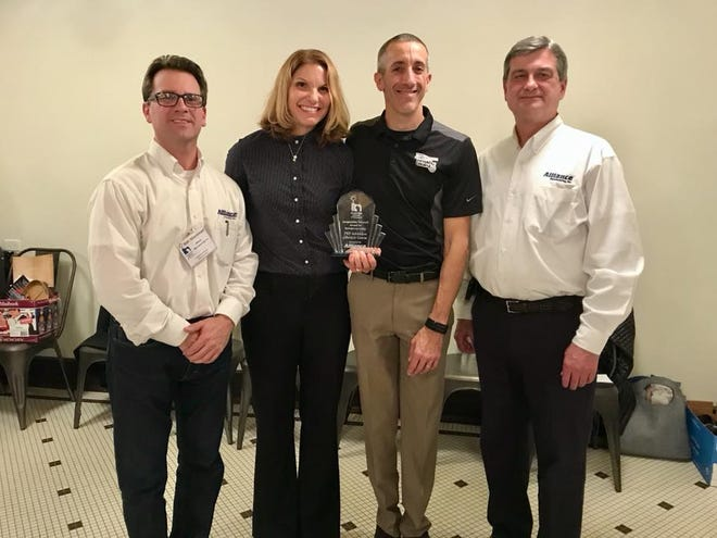 Melissa and Joe Schmidt, middle, of TNT Adventure Obstacle Course stand with award sponsors Alliance Manufacturing, Inc. represented by Ken Manninen, far left, and Jeff Brouchoud, far right.