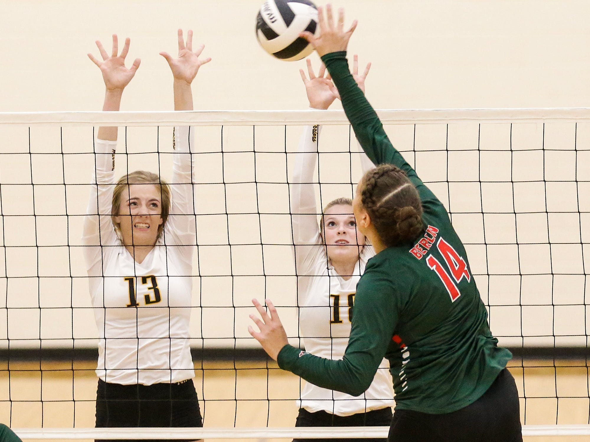 Waupun High School volleyball's McKenna Cunningham and Makenna Harmsen go up to block the ball against Berlin High School's Bria Reiser during their WIAA regional quarter-final playoff game Tuesday, Oct. 16, 2018, in Waupun.