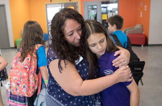 Lori McLain embraces student Grace Hilliker,12, at the end of classes. Hilliker gave McLain an appreciative note.
