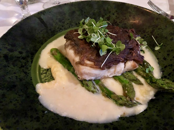 Potato-crusted mangrove snapper with thick spears of asparagus in a light lemon-cream sauce.