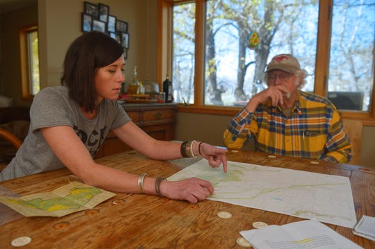 "Rachael Spangelo, an employee at McFarland White Ranch, Mont., points out sections of ranch land that are surrounded by national forest an inaccessible by vehicle. ""They need to be managed,"" she said."