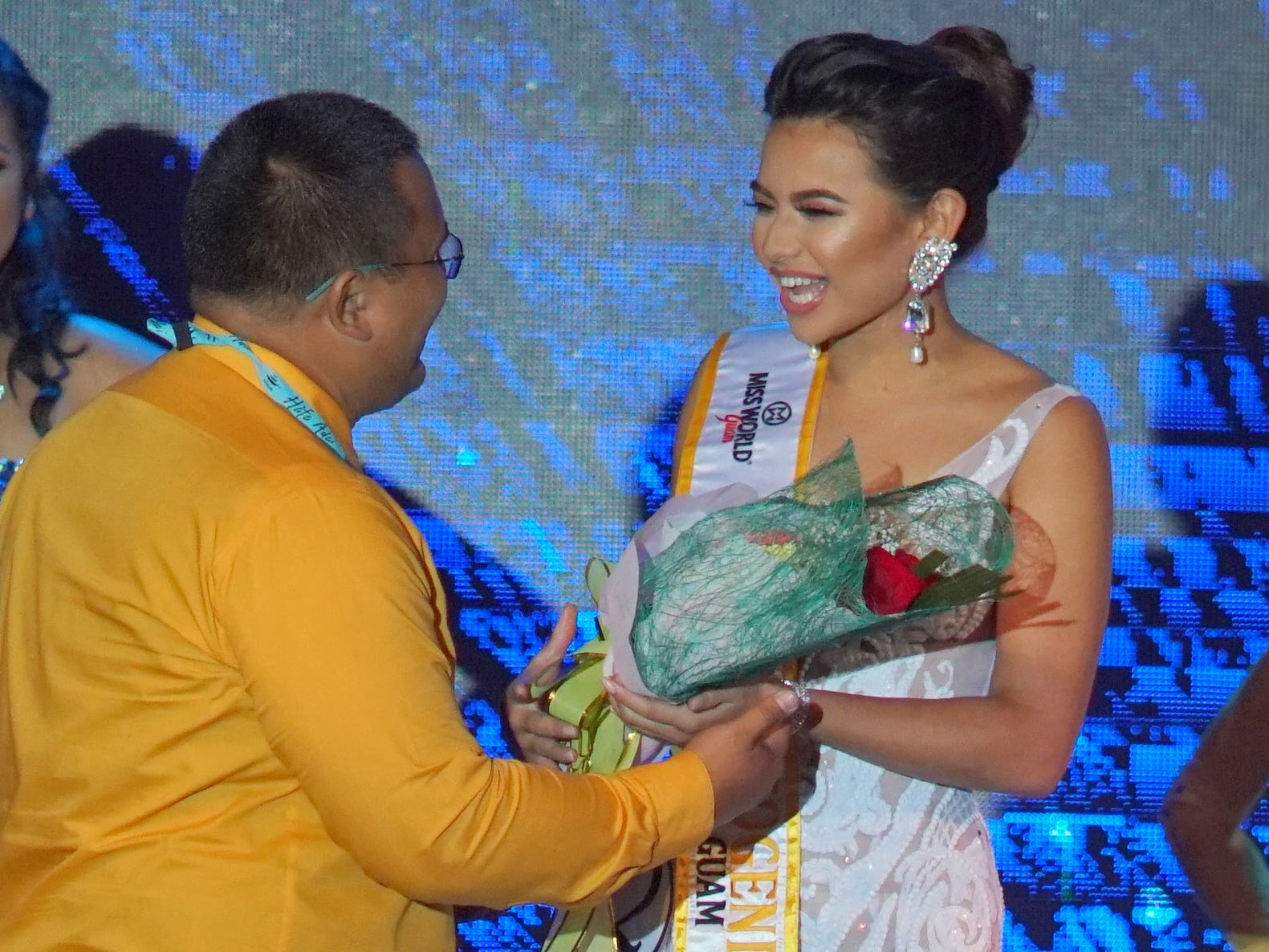 Photographer John Balbin presents flowers to Contestant #2, Gianna Camacho Sgambelluri. She won the Miss Photogenic award during the 2018 Miss World Guam pageant held at Sheraton Laguna Guam Resort.