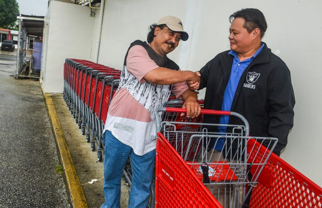 Employee Arikat Mwarepue, left, and butcher manager Christopher Castor shake hands on Wednesday, Oct. 17, 2018, near the spot where Mwarepue found an abandoned women's purse, the previous day, lying on the ground by the row of shopping carts behind the Happy Mart in Barrigada. The bag, which was reported purse-snatched from a visiting Chinese tourist in Tumon, still contained the victim's passport and airline tickets. Castor said he was able to contact the bag's owner through the airline and the thankful victim was able to catch her flight, which was scheduled to depart just hours after the discovery and return of the bag along with some of its contents.