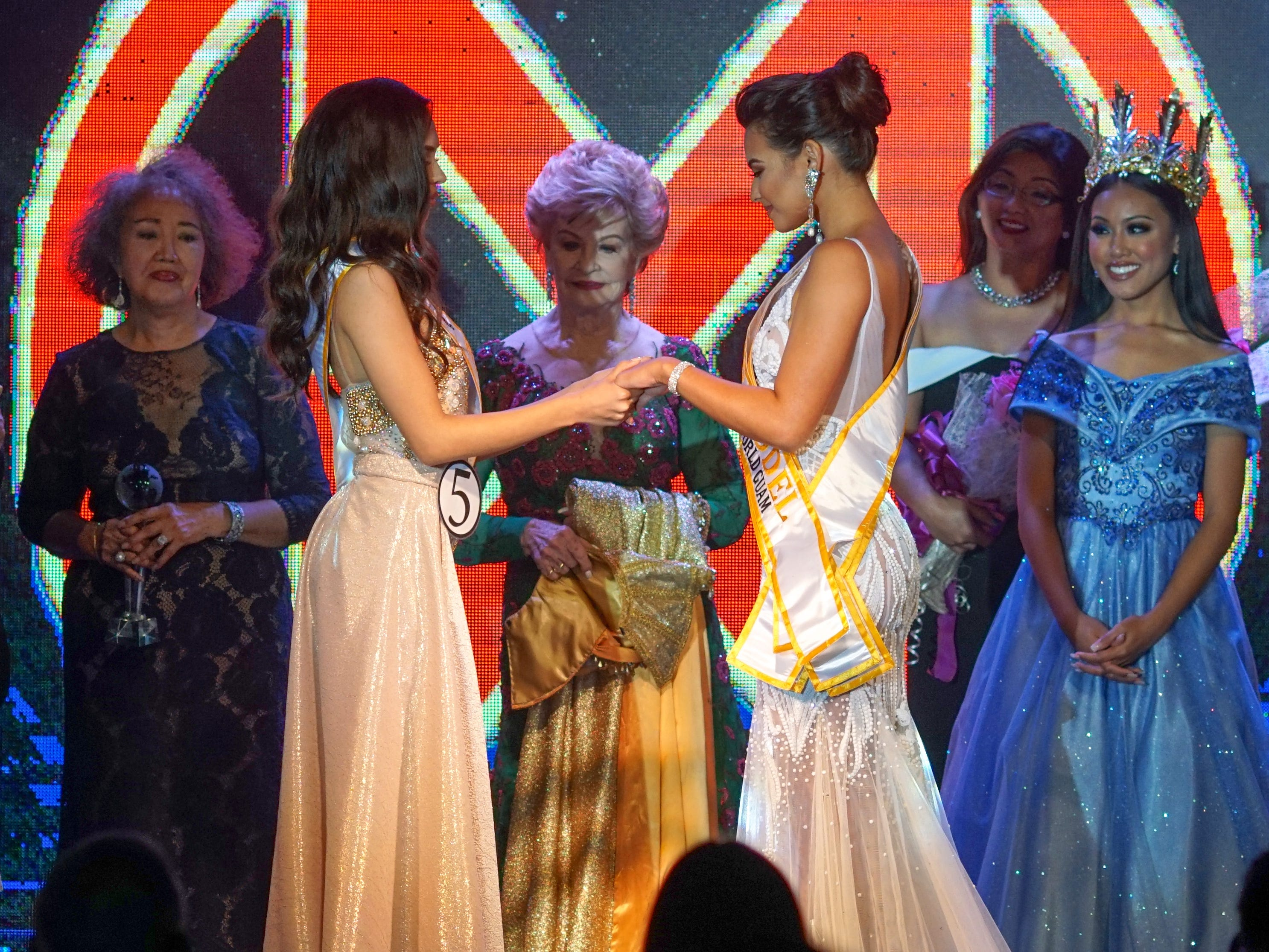 Madeleine Bordallo stands between the remaining two  Contestants #5 Cyndal Abad and #2 Gianna Camacho Sgambelluri as they await the winner to be called as the 2018 Miss World Guam pageant Queen.