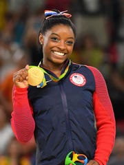 Simone Biles shows off one of the four gold medals she won at the Rio Olympics.