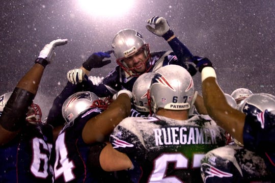 New England Patriots kicker Adam Vinatieri, top, is hoisted to the shoulders of his teammates after his game-winning overtime field goal against the Oakland Raiders in the AFC Divisional Playoff game at Foxboro Stadium, in Foxboro, Mass., Saturday Jan. 19, 2002.  The Patriots won 16-13. (AP Photo/Charles Krupa)