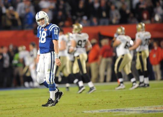 Indianapolis Colts quarterback Peyton Manning looks dejected as Saint Tracy Porter runs back an interception for a fourth quarter touchdown as the New Orleans bench erupts in the Super Bowl in Miami Sunday, Feb. 7, 2010. (Matt Kryger / The Star)