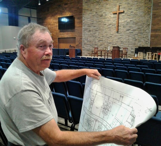 Building committee chairman Glenn Siders discusses blueprints in the new sanctuary at the new North Liberty Methodist church. It offers comfortable chairs instead of pews, the warm blue color contrasting nicely with a huge stone and wood chancel wall.