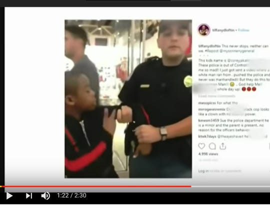 This image shows 12-year-old Mississippi native Corey Jackson (left) being detained by a police officer in Georgia.
