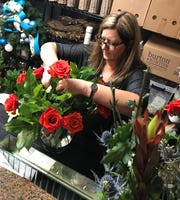 Gina Diamond, owner of Gina Diamond's Flower Co. in Madison, works on the design for an arrangement of roses.