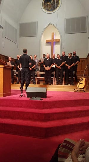 A group of men sing during a worship service at an Adult and Teen Challenge graduation ceremony at First Baptist Lexington.