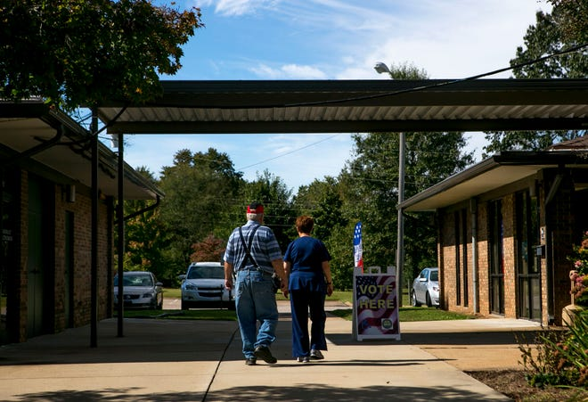 Residents walk to the main building where voting booths are stationed at Madison County Agricultural Complex in Jackson, Tenn., on Wednesday, Oct. 17, 2018.