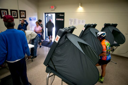 A woman in cycling clothing and helmet casts her ballot during early voting at Madison County Agricultural Complex in Jackson, Tenn., on Wednesday, Oct. 17, 2018.