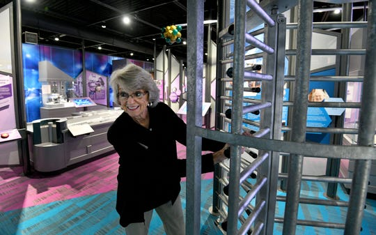 Educator Pat Fitchpatrick demonstrates an old turnstile exhibit at the new American Museum of Science and Energy.