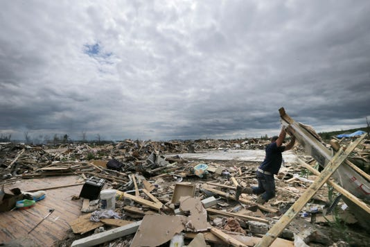 Dustin Shaw lifts debris as he searches through what is left of his sister's house at Parkwood Meadows neighborhood after a tornado in Vilonia, Ark.
