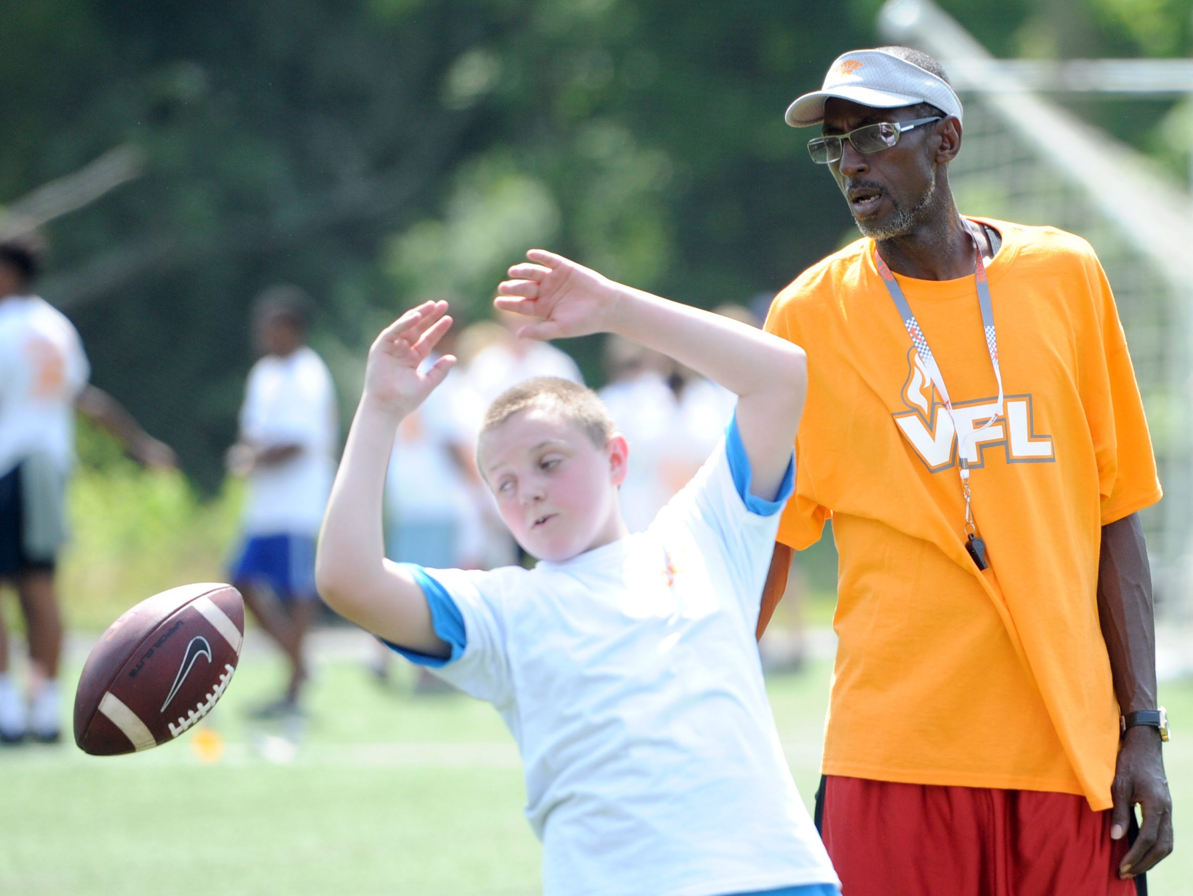Former Tennessee quarterback Tony Robinson, right, watches as Mark Foust, 12, attempts a catch during the sixth annual Camp 76, featuring former University of Tennessee and NFL players at Johnny Long Training Academy on Saturday, June 4, 2016. Camp 76 is a continuing effort to keep the legacy of former UT football player Harry Galbreath, who died in 2010 at age 45, alive for young athletes and generations to come.