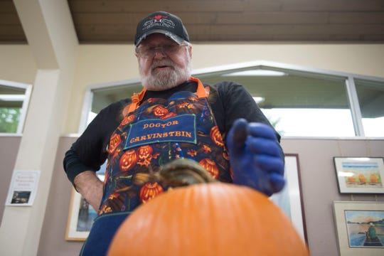 Artist Ken Clayton, also known as Dr. Carvinstein, looks down at a pumpkin he is about to carve at the Fountain City Art Center on Oct. 16, 2018. Clayton has been carving for over 50 years.