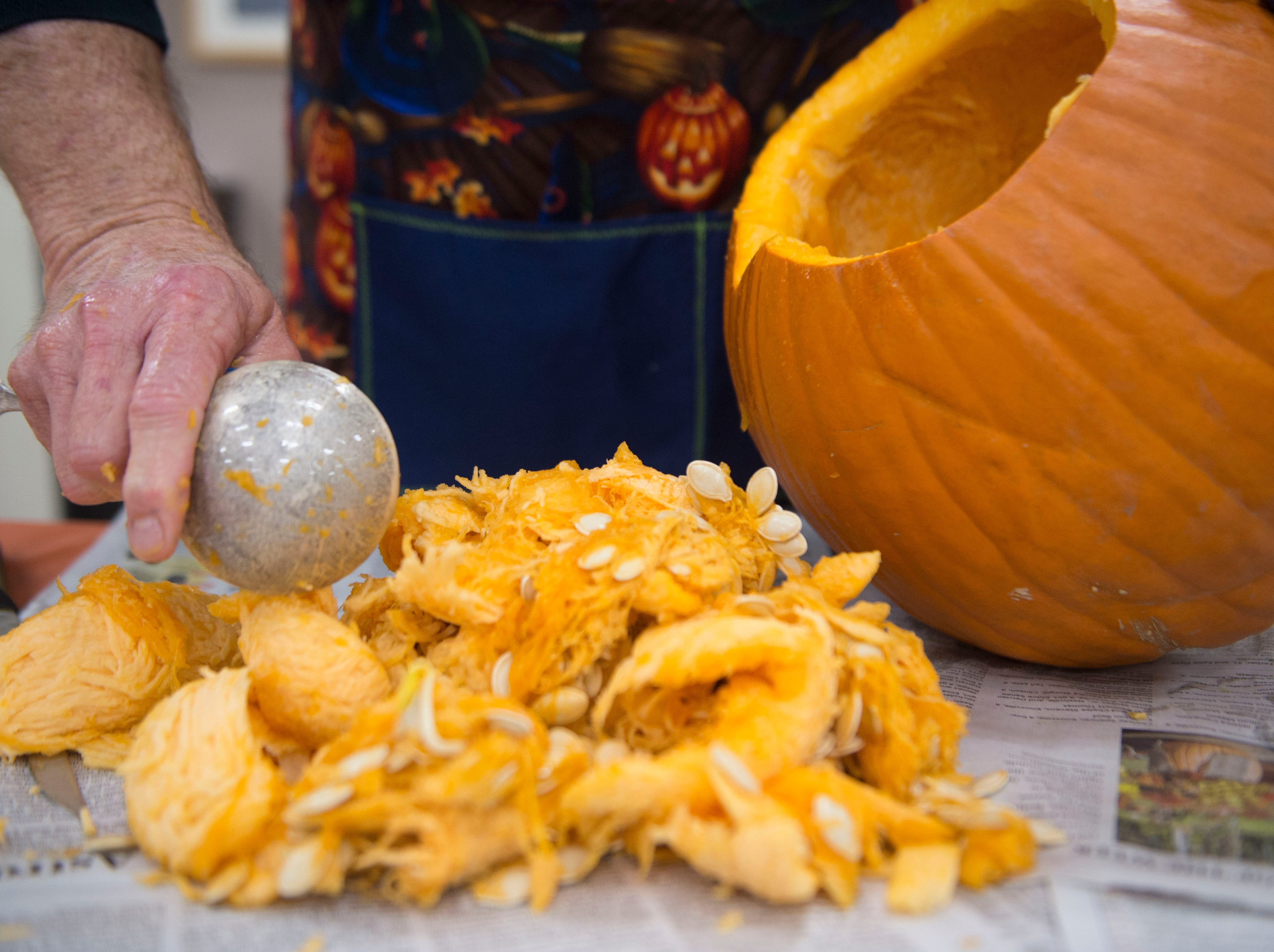 Artist Ken Clayton, also know as Dr. Carvinstein scoops the seeds out of a pumpkin he is carving at the Fountain City Art Center, Tuesday, Oct. 16, 2018. Clayton has been carving for over 50 years.