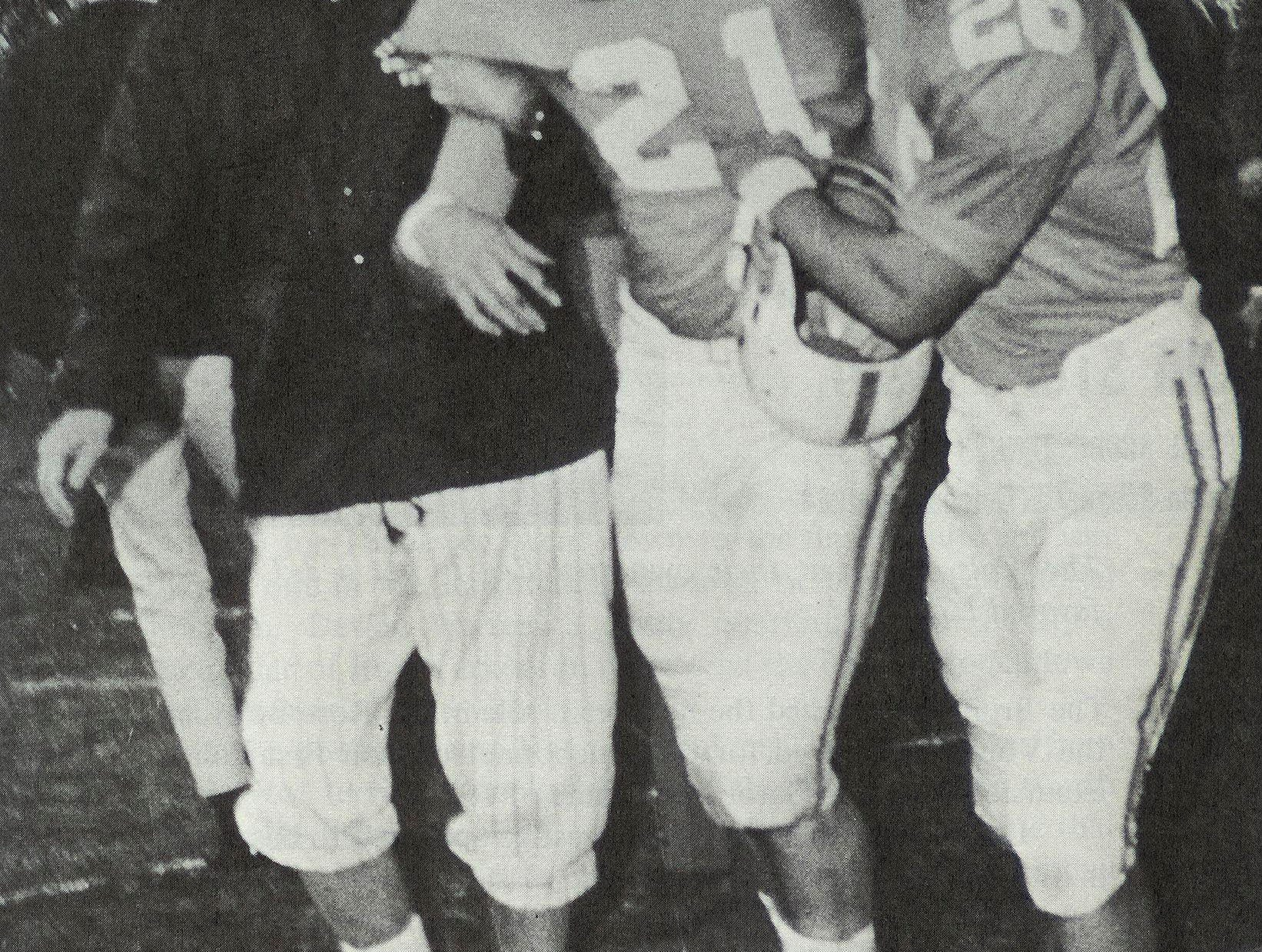 Trainer Mickey O'Brien, left, and teammate Albert Dorsey, right, help Tennessee defensive back Bob Petrella off the field after the Vols' 37-34 win over UCLA on Dec. 4, 1965, in Memphis. Petrella had the game-clinching interception off Bruin quarterback Gary Beban and had been flattened by Bruins fullback Paul Horgan on the UCLA sideline.