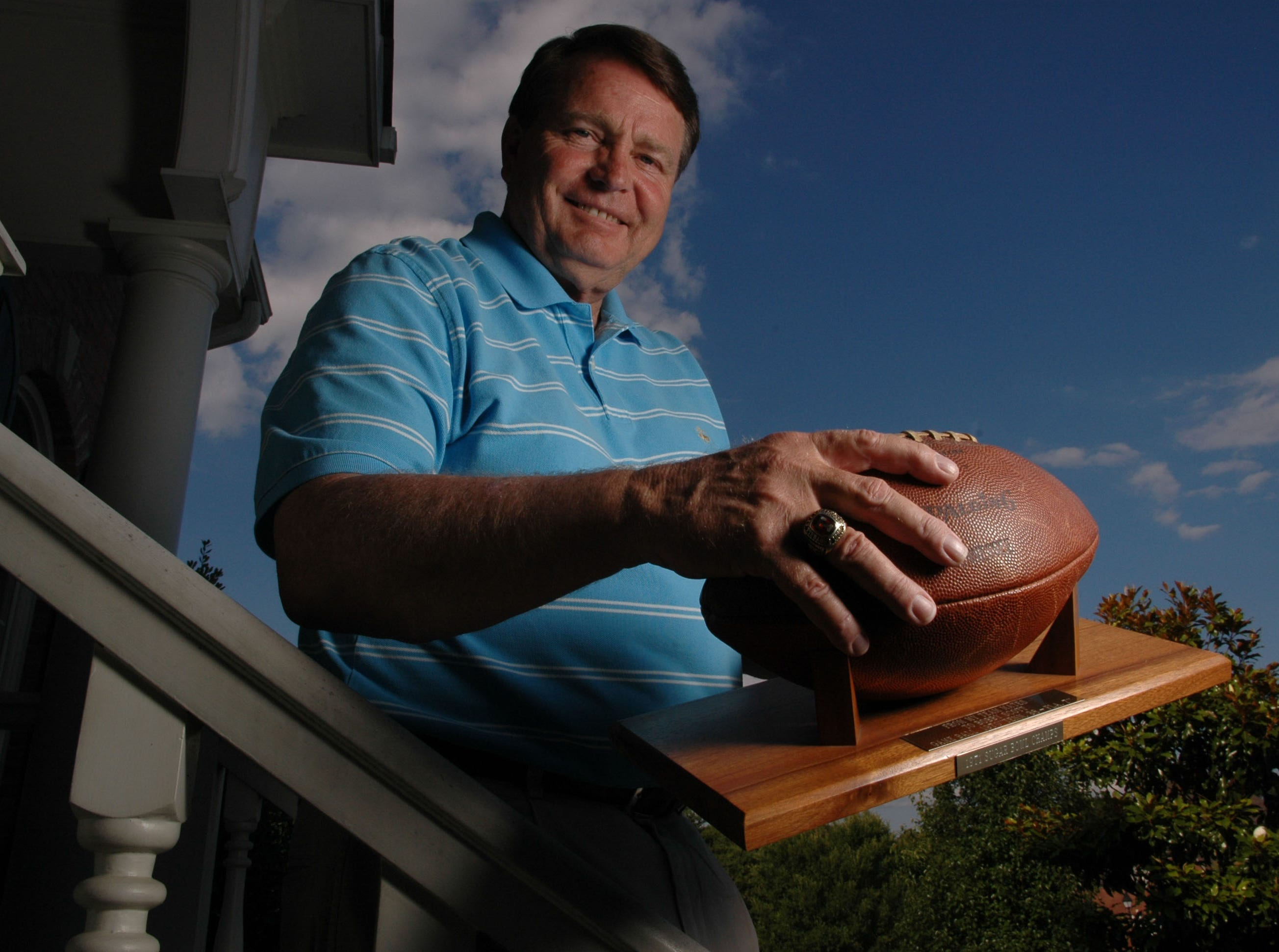 """Bobby Scott, who played quarterback at the University of Tennessee and in the NFL holds the game ball from UT""""s 38-7 victory over Florida in Knoxville in 1971 while posing for a photo on his front porch in Knoxville.  On his hand he wears his 1969 SEC Championship ring."""