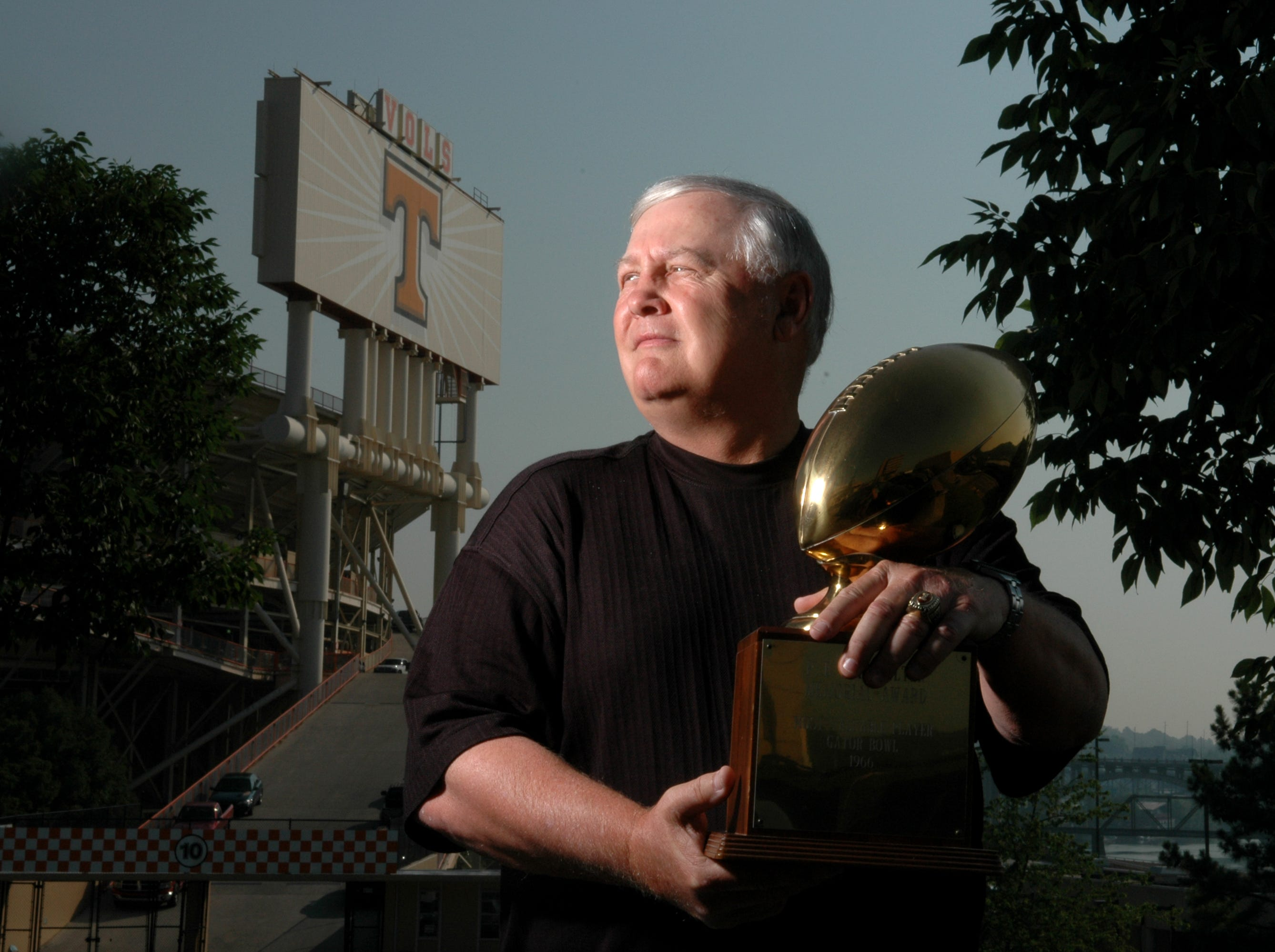 Dewey Warren, former UT quarterback, holds his 1966 Gator Bowl MVP trophy in front of Neyland Stadium Friday.  Warren is being inducted into the KNoxville Sports Hall of Fame next month.