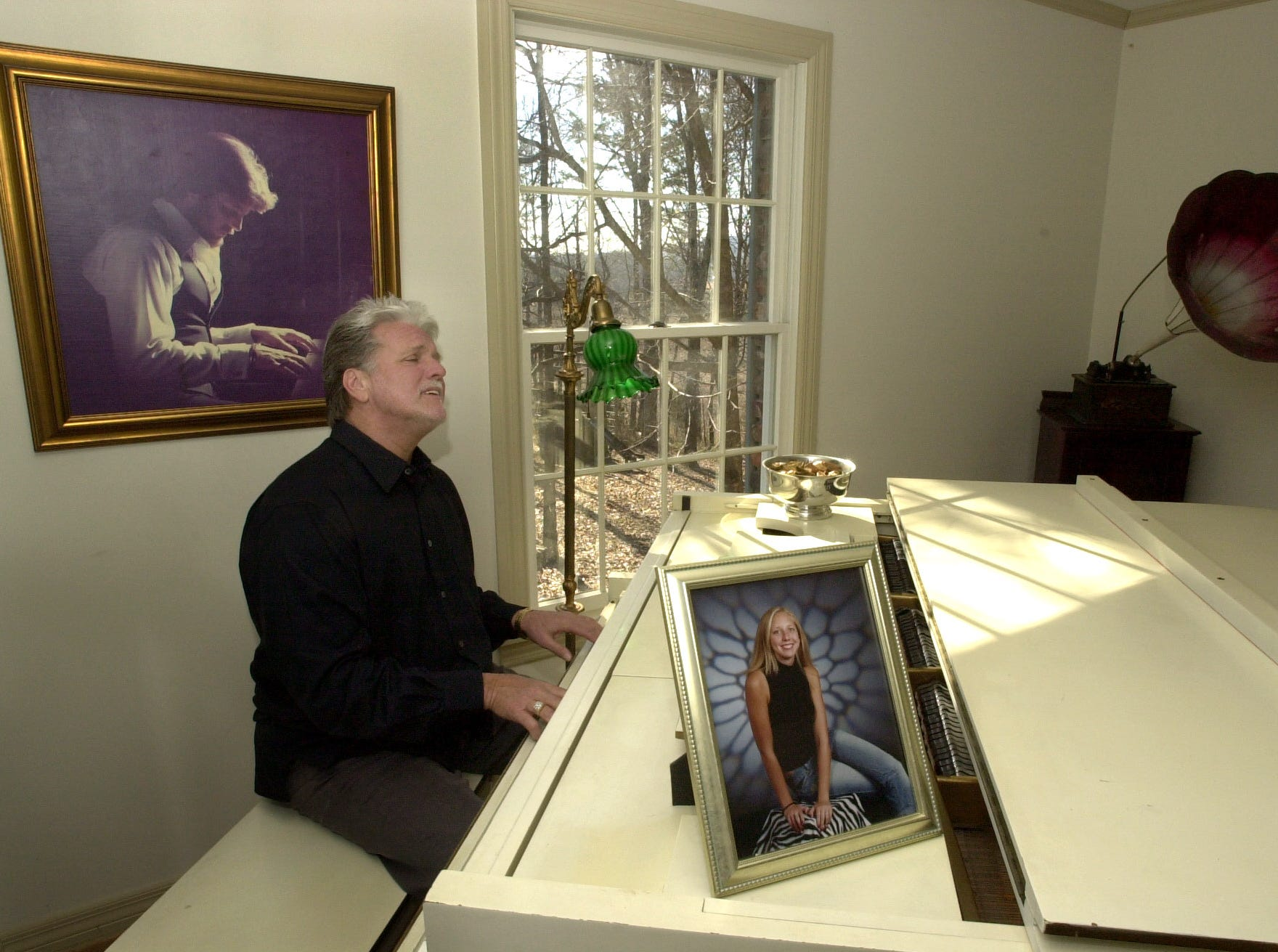 "Country music performer Con Hunley plays a tune in his North Knoxville home Wednesday.  In the foreground is a picture of his daughter Brittany Hunley, 18, who is a freshman at the University of Tennessee and hanging on his wall is a picture of himself from 1975, when his career was on the rise.  Since then his career has been a roller coaster ride, now peaking again with the release of an album called ""Sweet Memories."""