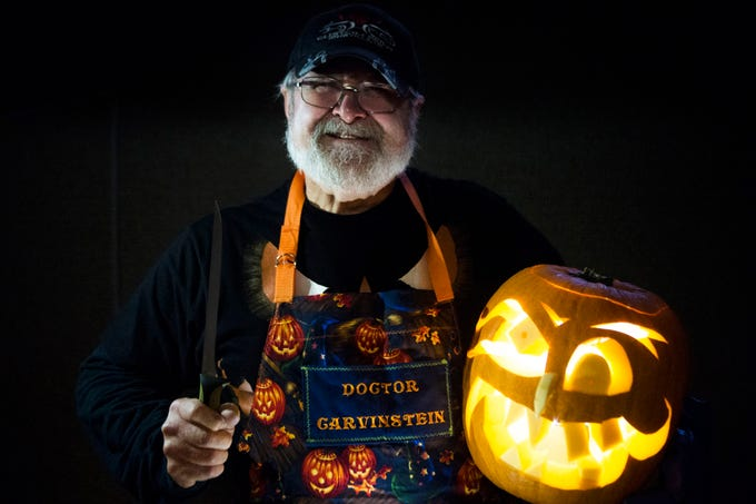 Artist Ken Clayton, also known as Dr. Carvinstein, poses for a photo with a pumpkin he carved at the Fountain City Art Center, Tuesday, Oct. 16, 2018. Clayton has been carving for over 50 years.