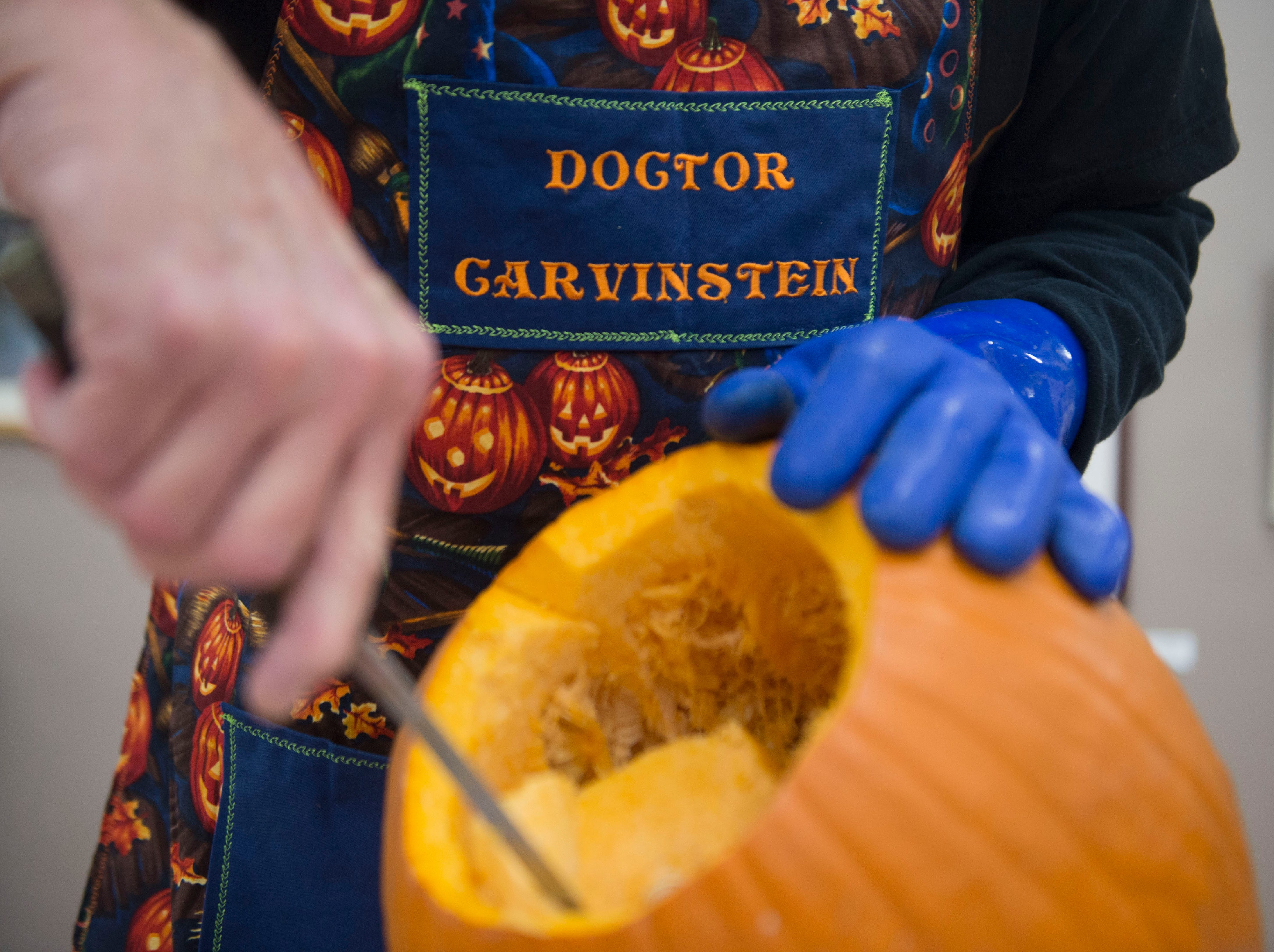 Artist Ken Clayton, also known as Dr. Carvinstein, scoops the seeds out of a pumpkin he is carving at the Fountain City Art Center, Tuesday, Oct. 16, 2018. Clayton has been carving for over 50 years.