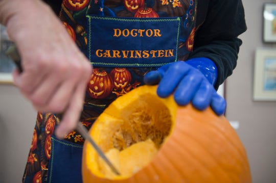 Artist Ken Clayton, aka Dr. Carvinstein, scoops the seeds out of a pumpkin at the Fountain City Art Center on Oct. 16.