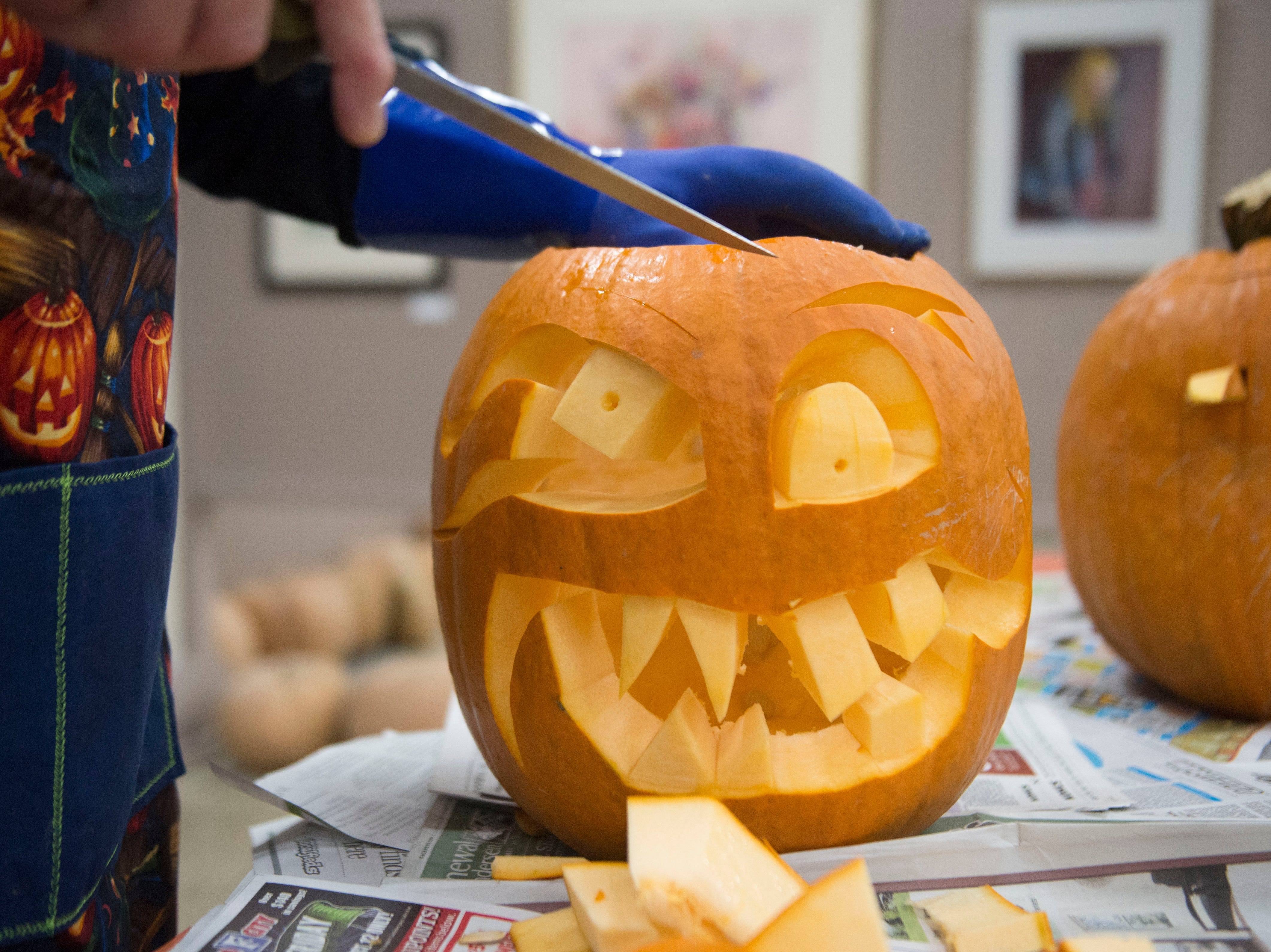 Artist Ken Clayton, also known as Dr. Carvinstein, carves a pumpkin at the Fountain City Art Center on Oct. 16, 2018. Clayton has been carving for over 50 years.