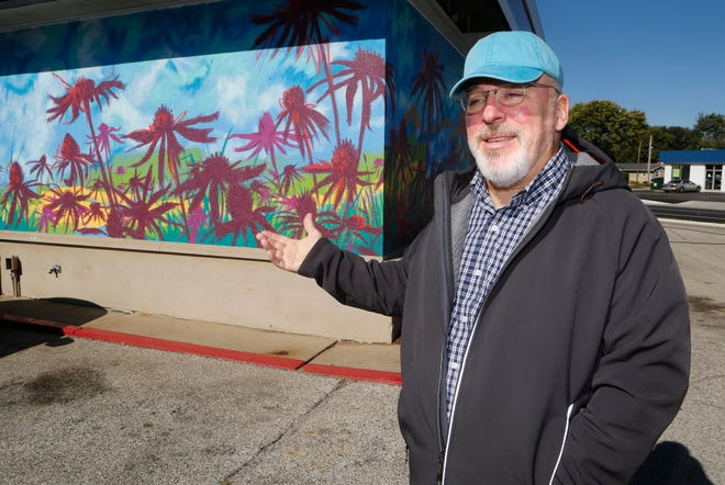 """Artist Craig Martin talks Wednesday, October 17, 2018, about the mural """"Tropical Wabash"""" he painted on the side of the Jiffy Lube at the corner of South Street and Earl Avenue in Lafayette. According to Lonnie J. Hinkle, COO of Jiffy Lube of Indiana, there are currently nine Jiffy Lube stores that feature murals with six more slated to receive artwork next."""