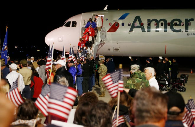 Veterans and their guardians taking part in the final Honor Flight are greet with cheers and flags as they arrive Tuesday, October 16, 2018, at Purdue Airport.