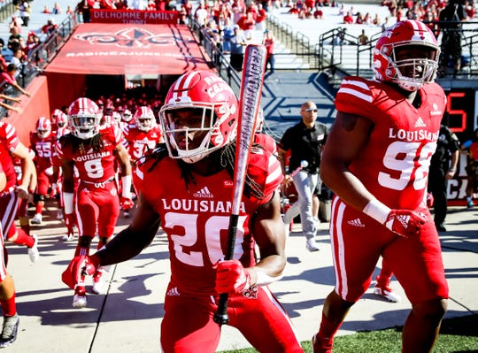 UL receiver Jarrod Bam Jackson helps lead the Ragin' Cajuns onto the field for their Homecoming win over New Mexico State last Saturday. Jackson had two touchdown catches in the 66-38 win.