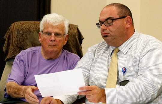 W. Allan Reid, left, and Kyle Farmer look at a piece of evidence submitted during a hearing challenging Kryssi Wichers' voter registration in the county Wednesday, Oct. 17, 2018, at the Fairfield County Board of Elections. Reid, Farmer and fellow B.O.E. member Paul Johnson voted unanimously to dismiss the claim by Chris Chapman.