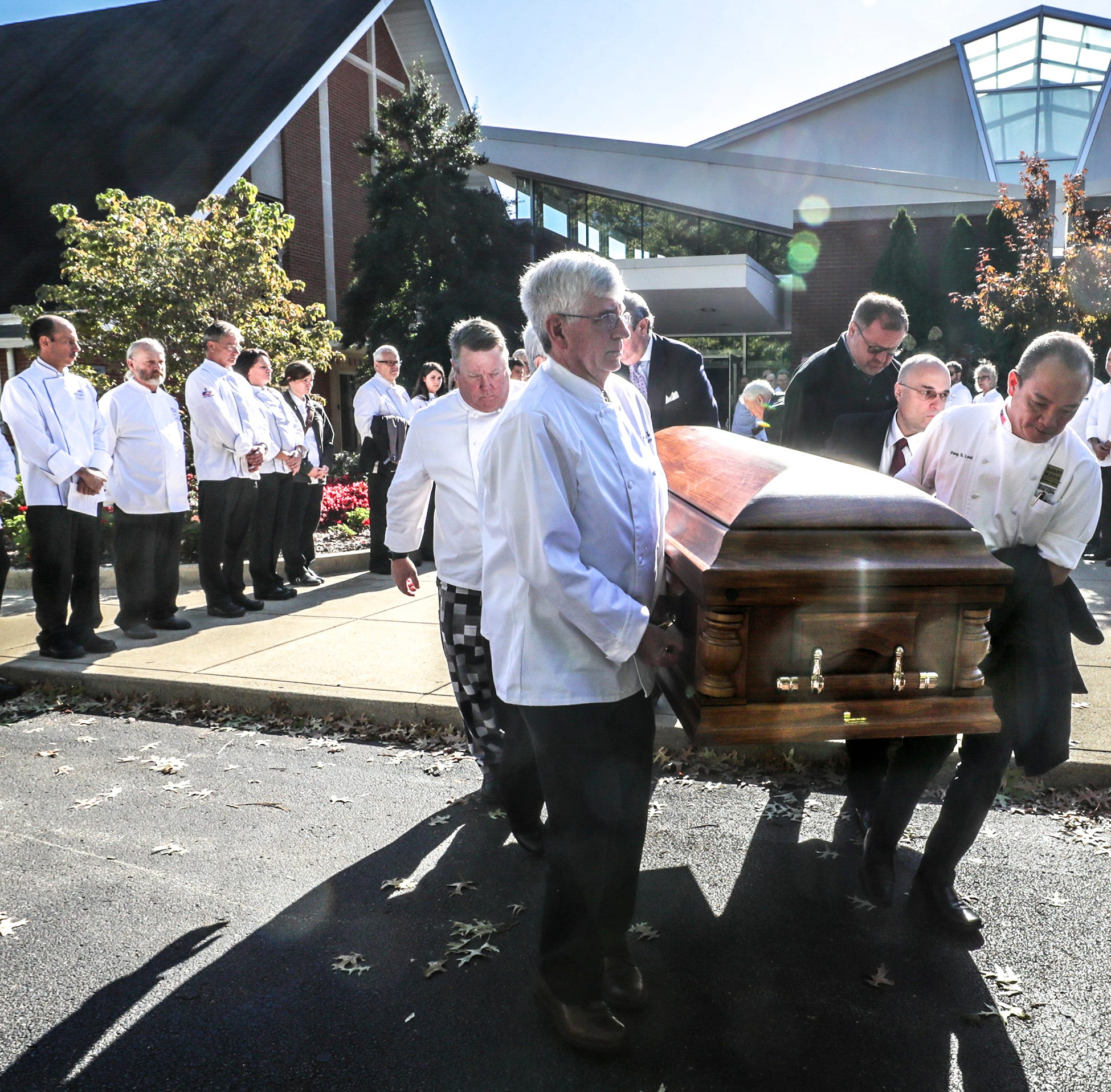 Local chefs serve as pallbearers as they escort the casket of chef Dean Corbett to a waiting hearse after funeral services at St. Albert the Great Church on Wednesday morning.  Chefs wearing white coats lined the walkway from the entrance to the church to the hearse. October 17, 2018