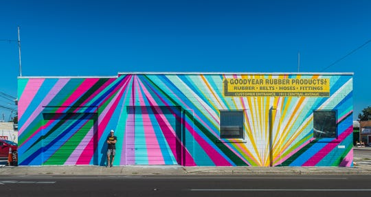 """Louisville artist Gibbs Rounsavall stands in from of his mural """"A New Day"""" located in St. Petersburg, Florida"""