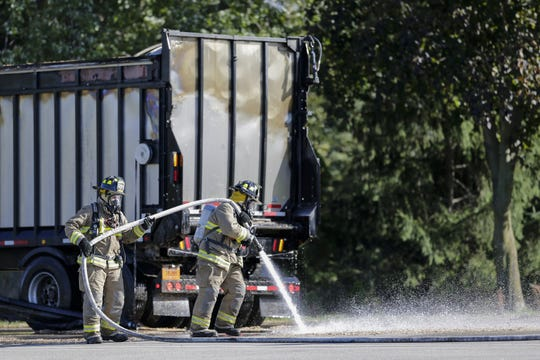 Reedsville Fire Department sprays the ground after putting out a fire in a semi trailer full of sawdust in the 300 block of Main Street Oct. 17 in Reedsville.