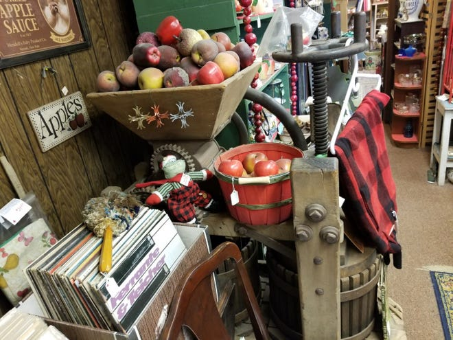 A cider press with fall decor resting on top of it sits just inside the entrance of Cider Mill Antique Shop south of Auburndale.