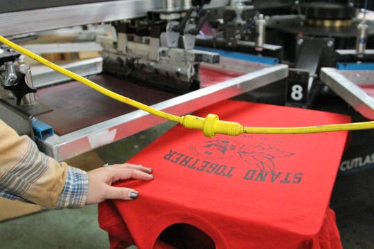 Kim Hessler, who co-owns Hessler's Screen Printing and More, rest her hand on a shirt created to honor Logan Stevens. As of Tuesday, her business had received about 300 orders for the shirts which will be worn at Friday's game.